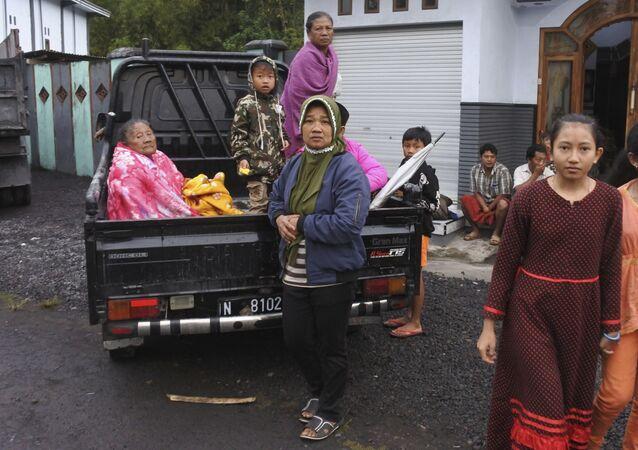 Mulheres indonésias sentam-se na parte de trás de um caminhão, se preparando para evacuação de suas casas, após erupção do Monte Semeru em Lumajang, província da ilha de Java, Indonésia, no dia 1º de dezembro 2020