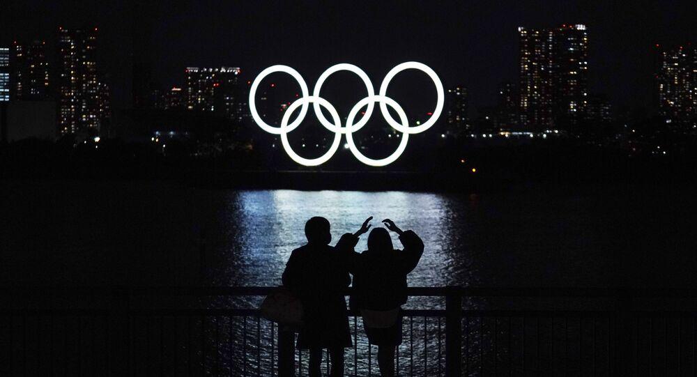 Pedestres olham os anéis olímpicos, iluminados na baía de Odaiba, em Tóquio, Japão, 1º de dezembro de 2020