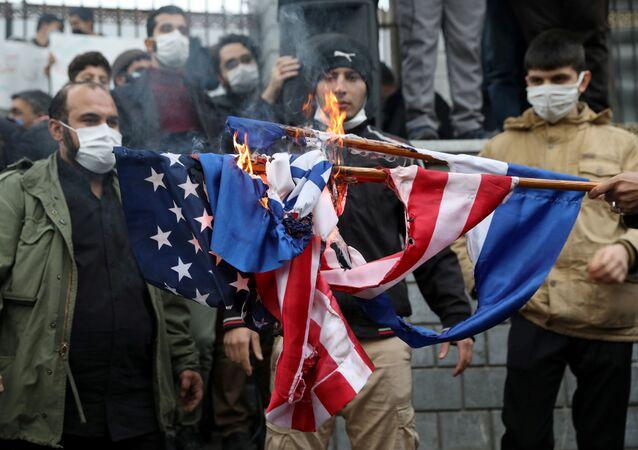 Manifestantes queimam bandeiras dos EUA e Israel em ato de repúdio ao assassinato de Mohsen Fakhrizadeh, Teerã, Irã, 28 de novembro de 2020