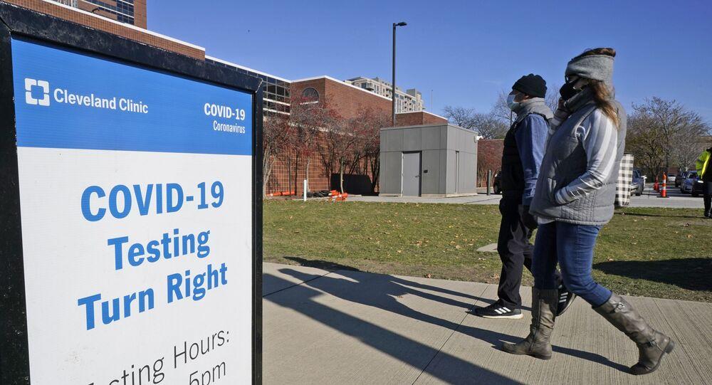 Duas pessoas passam perto da placa informativa sobre testes de COVID-19 na Clínica de Cleveland, no estado americano do Ohio