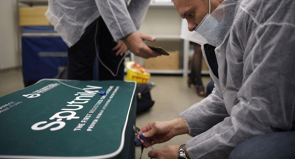 Agente de saúde abre caixa com doses da vacina contra a COVID-19 Sputnik V, em 2 de dezembro de 2020