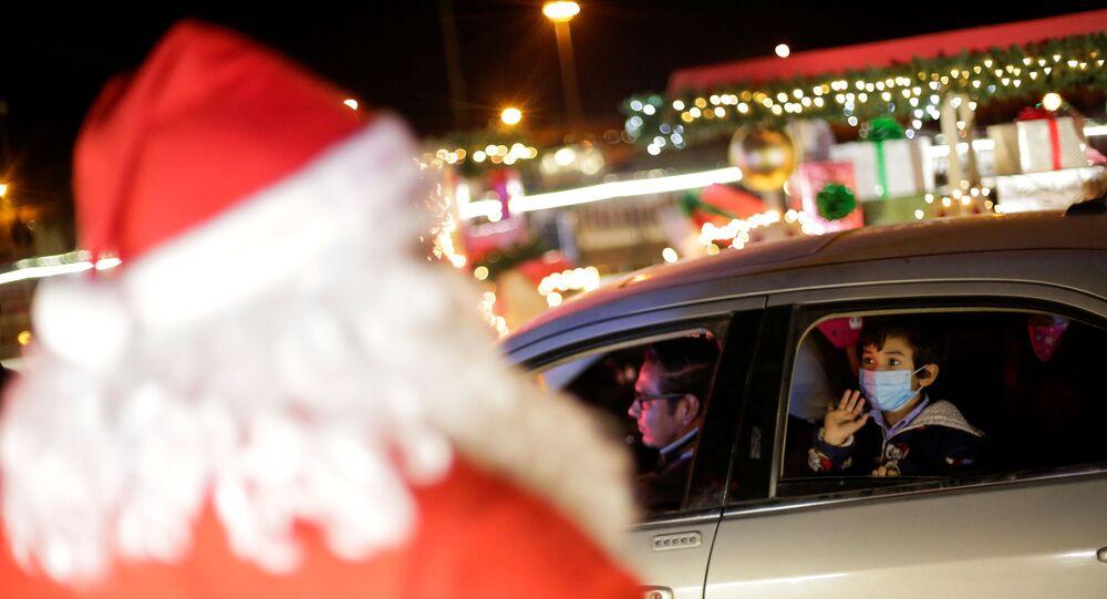 Criança acena para uma pessoa vestida de Papai Noel na cidade Juarez, no México