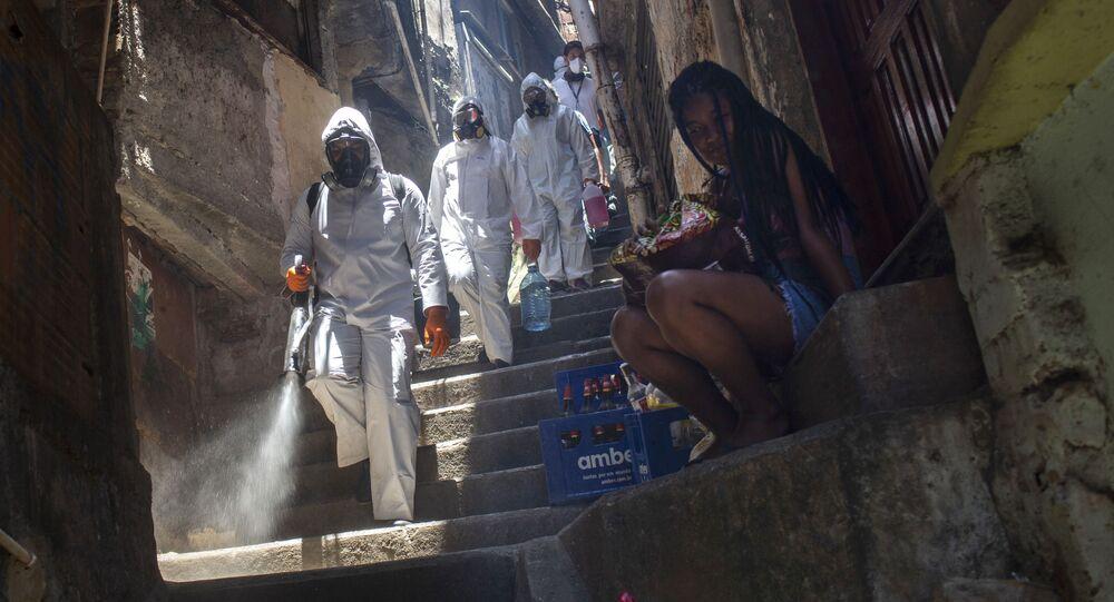 Voluntários desinfectam ruas na favela Santa Marta, no Rio de Janeiro