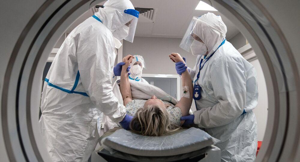 Profissionais de saúde e pacientes na sala de tomografia computadorizada em um hospital para doentes com COVID-19