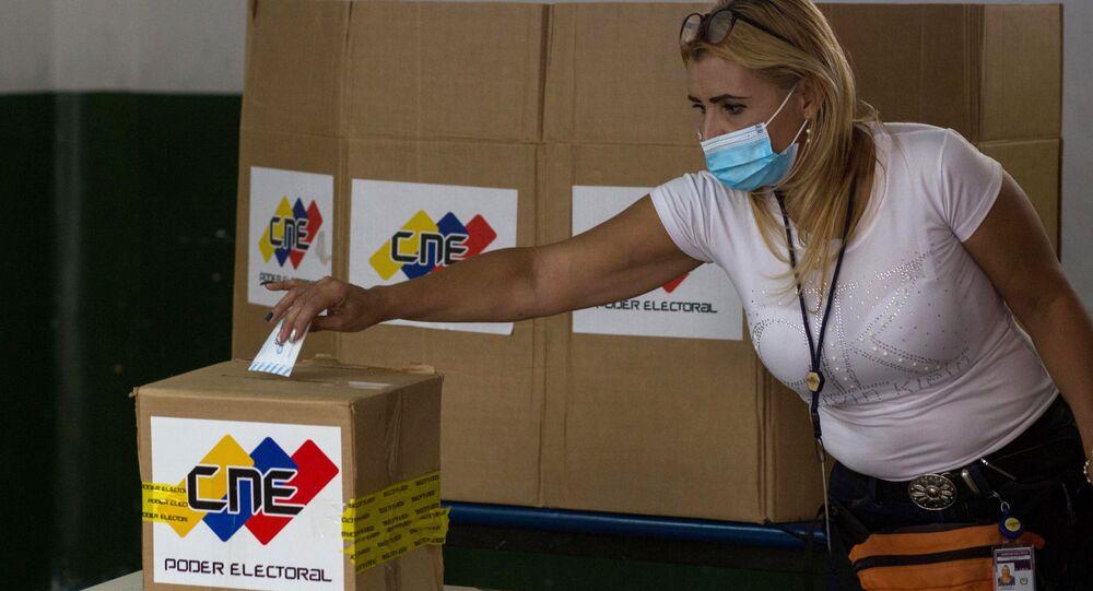 Em Caracas, na Venezuela, uma mulher deposita seu voto durante as preparações para eleições parlamentares venezuelanas, em 15 de novembro de 2020