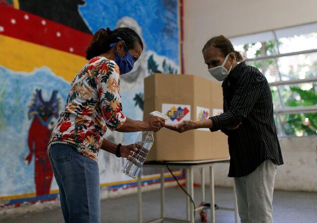 Eleitores higienizam as mãos em zona eleitoral em Caracas