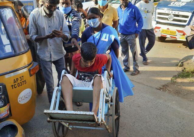 Garoto é levado em uma cadeira de rodas para o hospital do governo distrital em Eluru, estado de Andhra Pradesh, Índia, 6 de dezembro de 2020