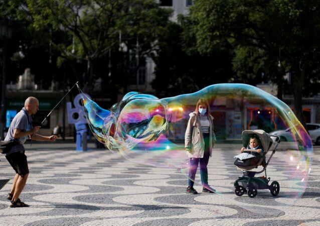 Artista de rua entretendo criança com bolhas de sabão na Praça D. Pedro IV em Lisboa, 31 de outubro de 2020 (foto de arquivo)
