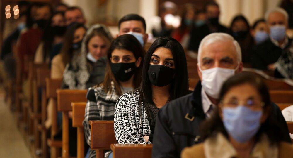 Pessoas de máscara mantendo o distanciamento social na missa antes de acender a árvore de Natal na Igreja do Sagrado Coração, Amã, Jordânia, 6 de dezembro de 2020