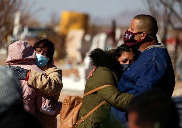 Parentes choram a morte de ente querido por COVID-19 num cemitério em Ciudad Juarez, no México no dia 2 de dezembro de 2020