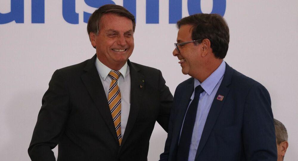 Em Brasília, o presidente brasileiro Jair Bolsonaro e o presidente da Embratur, Gilson Machado, se cumprimentam durante Cerimônia de Lançamento da Retomada do Turismo, no Palácio do Planalto, em 10 de novembro de 2020