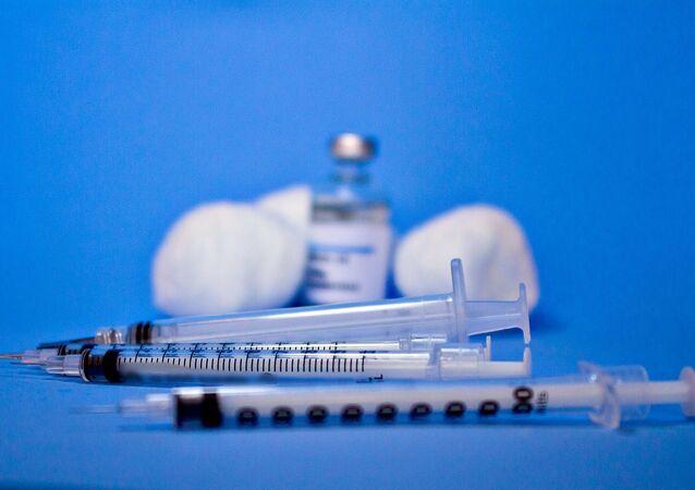 Imagem criativa usando fundo azul com frasco de vacina ao lado de insumos, em alusão à vacina contra o novo coronavírus (Covid-19)