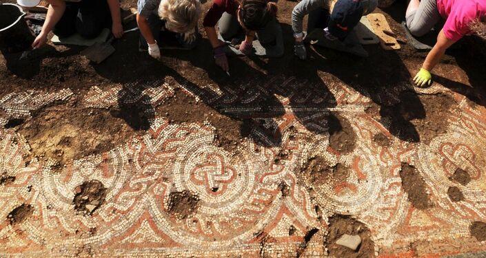 Uma equipe de voluntários escavando o mosaico