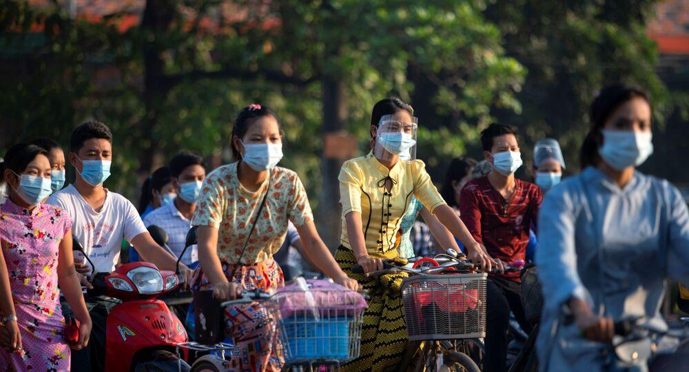 Pessoas usando máscaras andam de bicicleta na rua durante o surto de coronavírus em Yangon, Mianmar, 7 de dezembro de 2020