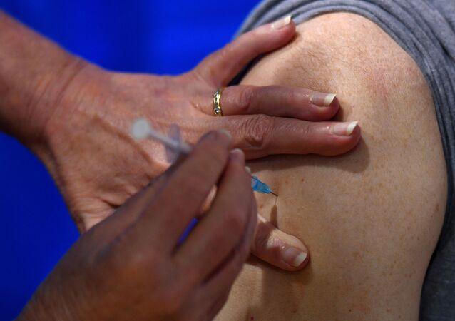 Enfermeira aplica vacina contra a COVID-19 em paciente em Cardiff no 1º dia de imunização no Reino Unido