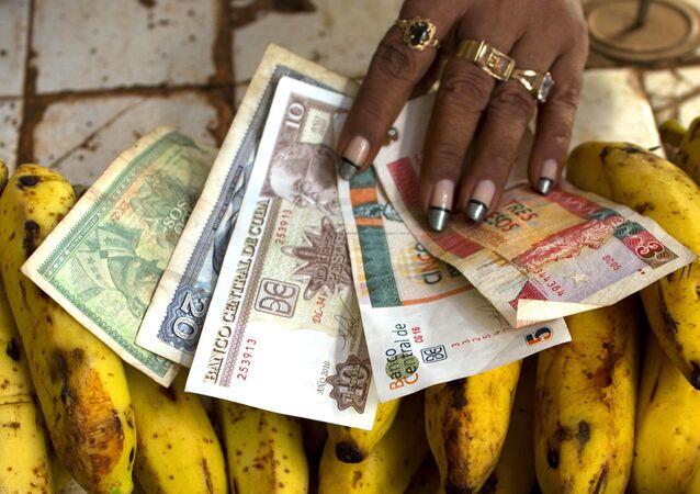 Vendedora exibe notas de peso cubano e peso conversível em um mercado de Havana (arquivo)
