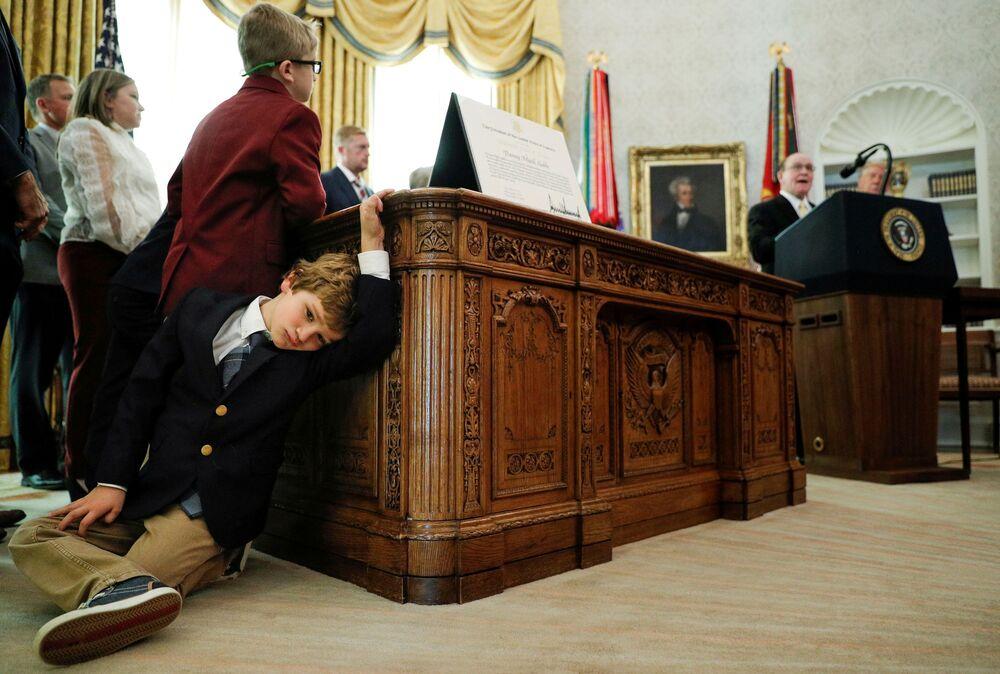 Neto de seis anos do atleta norte-americano Dan Gable espera enquanto seu avô discursa na Casa Branca, Washington