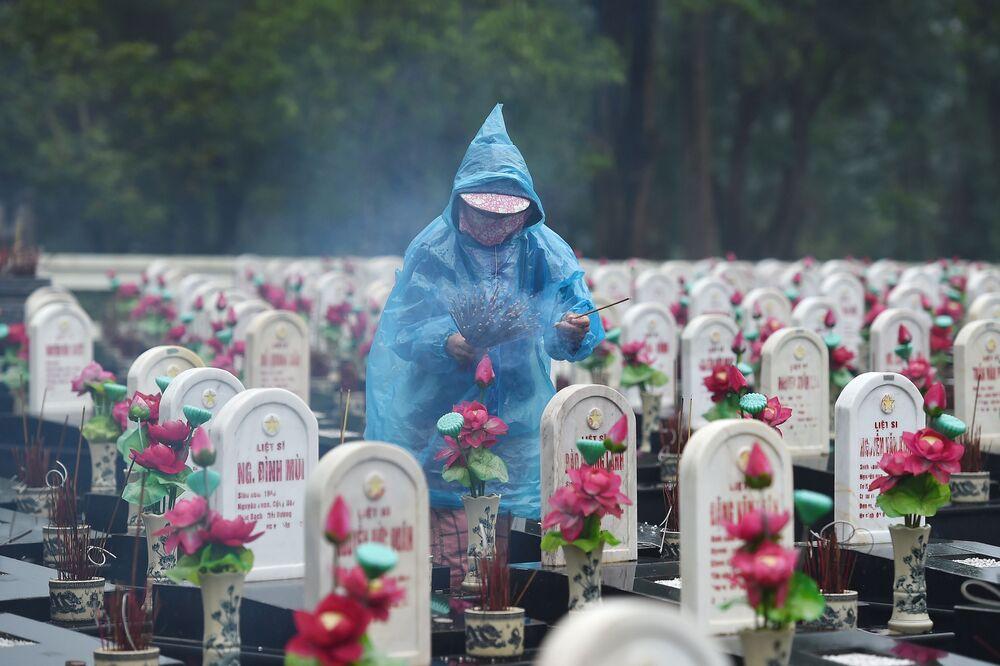 Visitante acende bastões aromáticos no cemitério dos mártires de Truong Son, Vietnã
