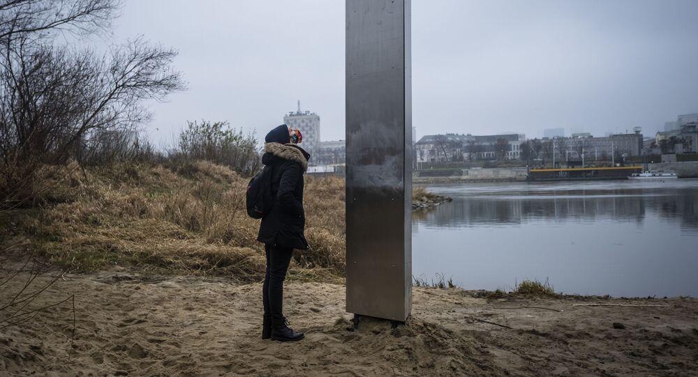 Mulher ao pé do monólito metálico que surgiu nas margens do rio Vístula, em Varsóvia, Polônia