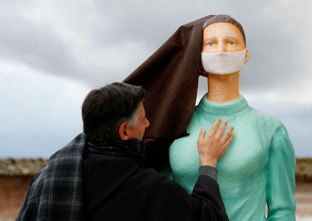 Sacerdote junto a figura de enfermeira no presépio instalado na praça da Basílica de S. Francisco de Assis, Itália
