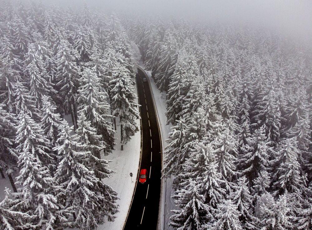 Carro passa entre árvores cobertas de neve na região de Taunus, perto de Frankfurt, Alemanha