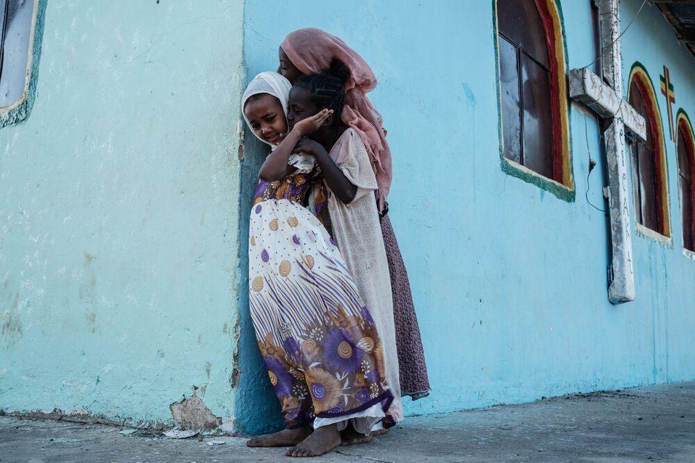 Crianças ao lado de uma igreja construída por antigos refugiados etíopes junto a um acampamento em Gedaref, no Sudão
