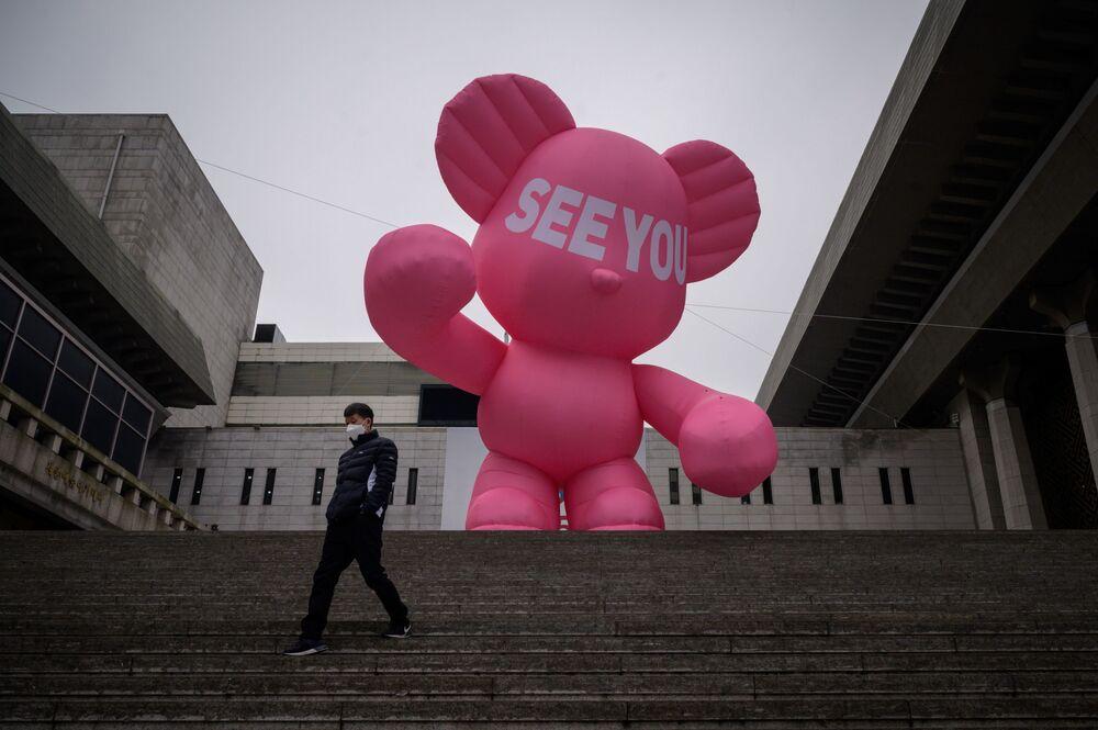 Homem com máscara protetora perto do teatro Sejong em Seul, Coreia do Sul