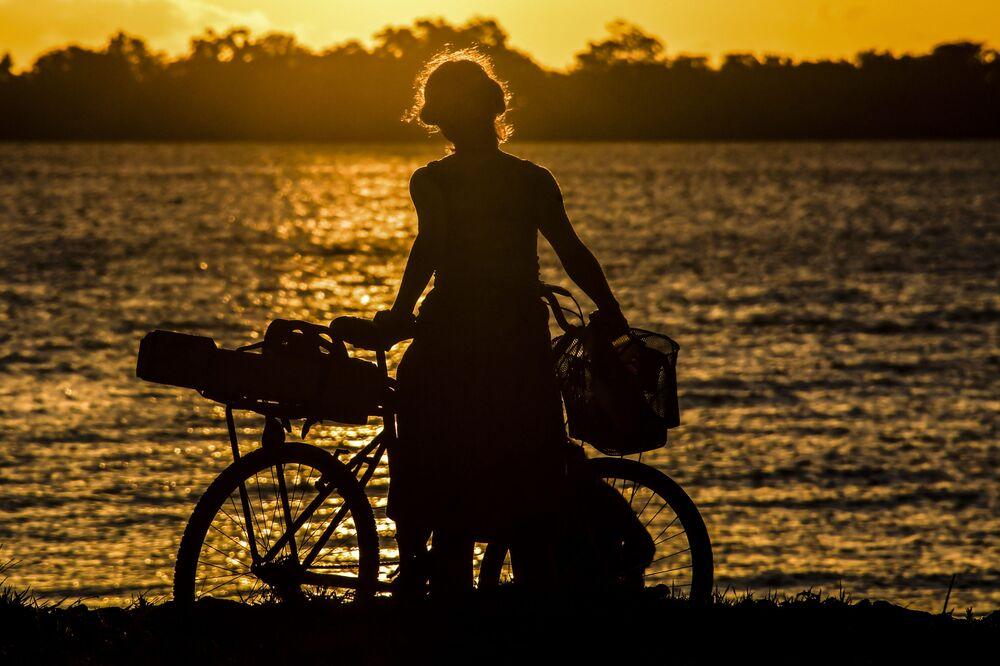 Ciclista admirando o pôr do sol no lago Guaiba, Porto Alegre, 8 de dezembro de 2020