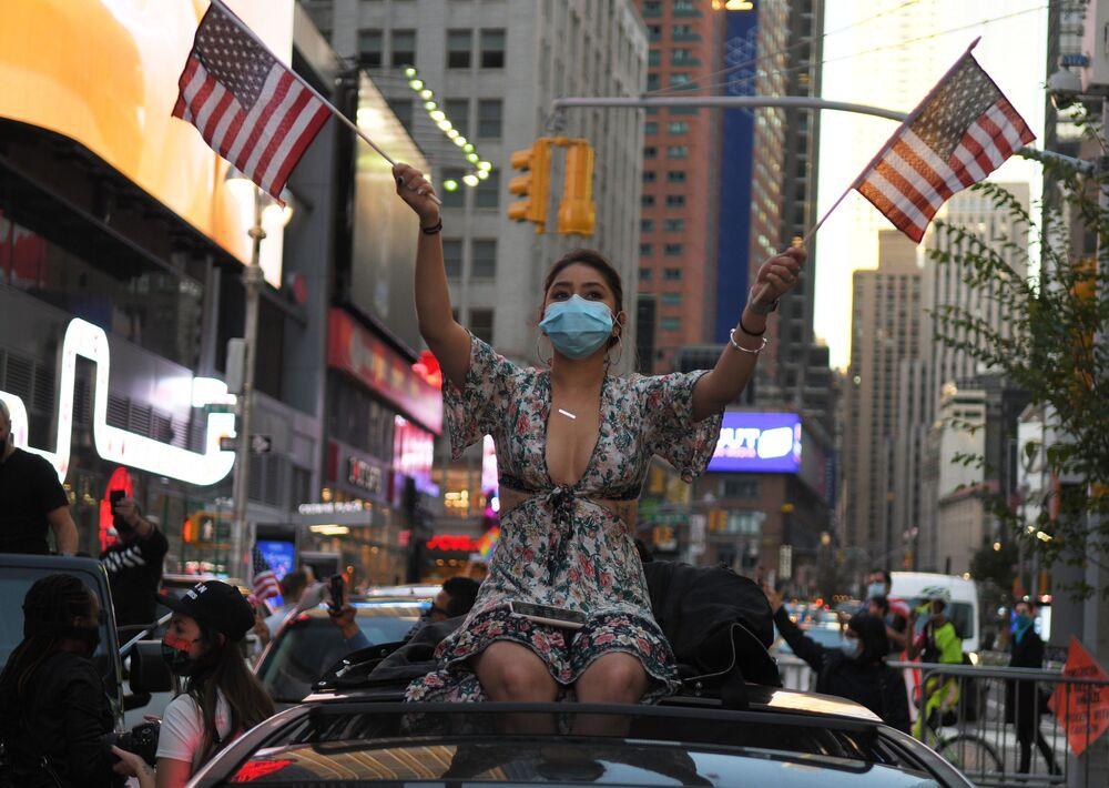 Jovem exibe bandeiras dos EUA no contexto das eleições americanas, cuja votação se deu em 3 de novembro