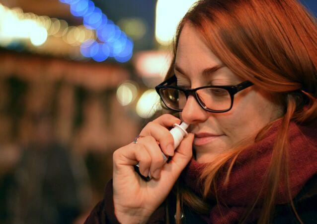 Mulher usando spray nasal (imagem referencial)