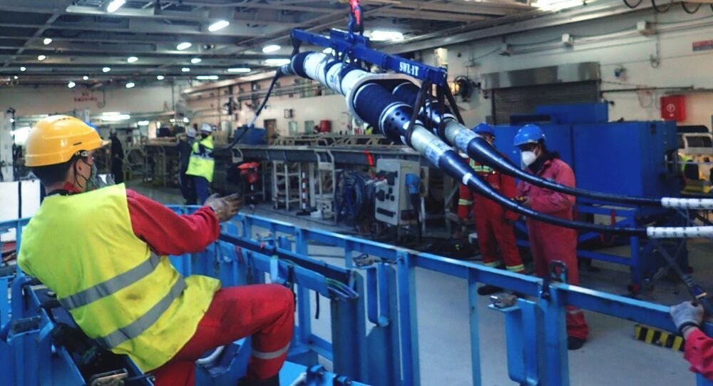 Funcionários da EllaLink fazem ajustes no cabo de fibra óptica