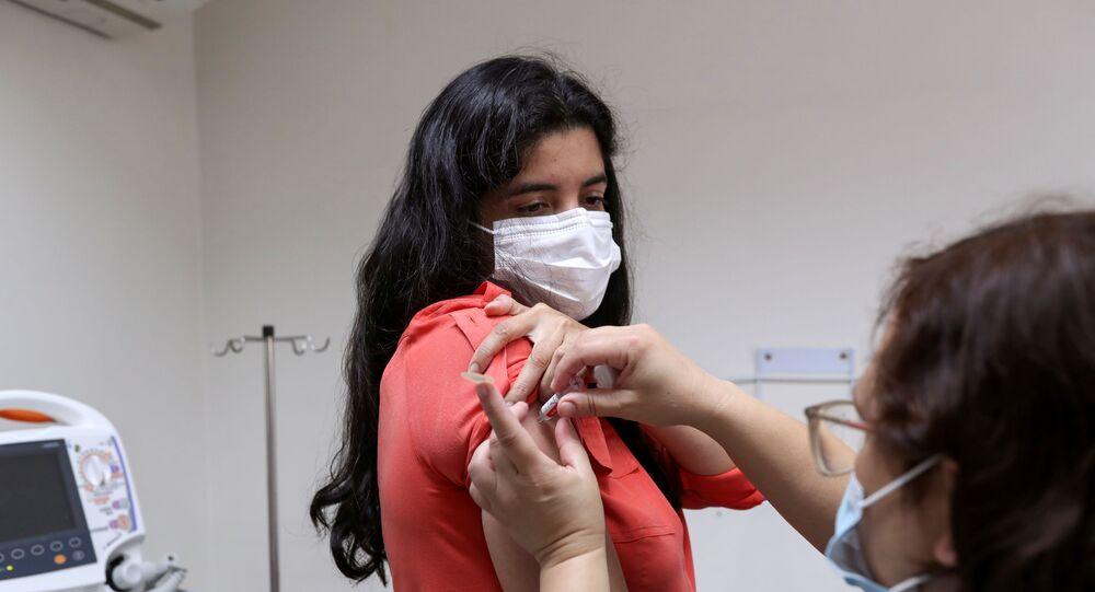 Agente de saúde recebe doses da vacina chinesa CoronaVac durante testes em São Paulo, 11 de dezembro de 2020