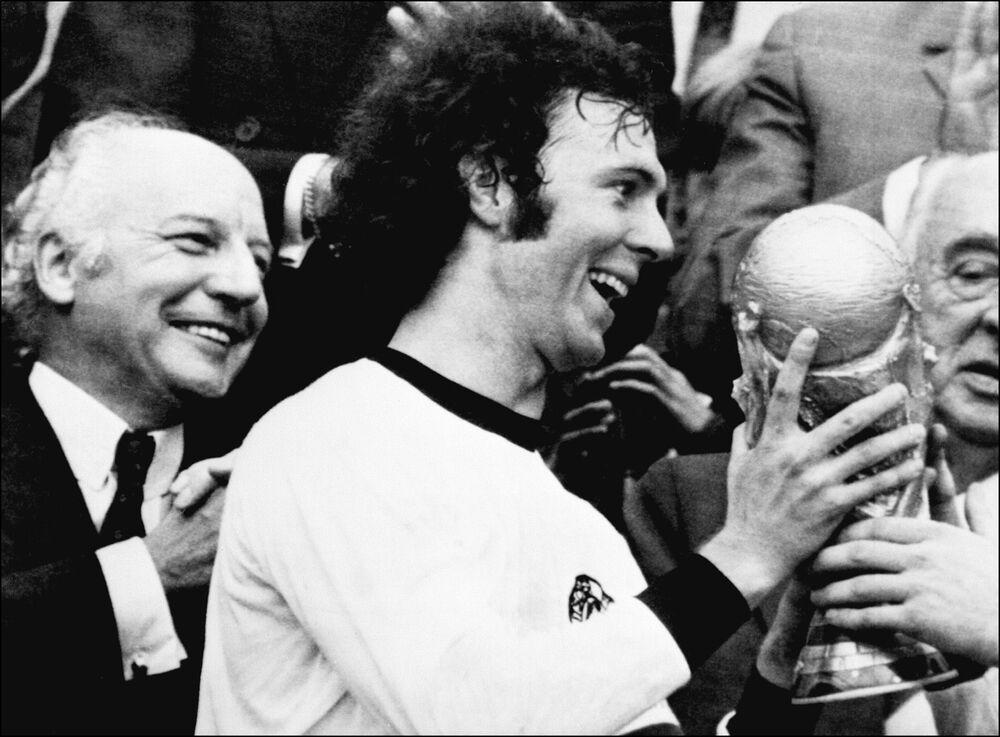 Jogador alemão e capitão da equipe, Franz Beckenbauer, recebe a taça da Copa do Mundo ganhada por seu time depois da vitória por 2 a 1 sobre Holanda em 7 de julho de 1974 no Estádio Olímpico de Munique, enquanto o presidente da Alemanha Ocidental, Walter Scheel, aplaude