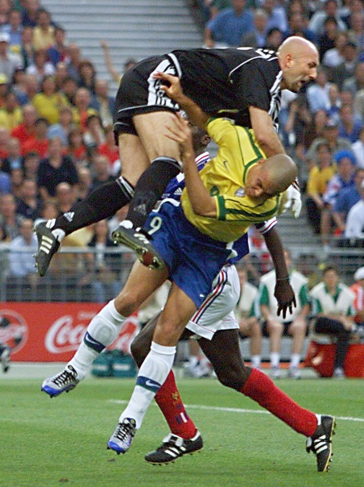 Goleiro francês Fabien Barthez salta sobre Ronaldo Fenômeno em 12 julho de 1998 no Estádio da França de Saint-Denis durante final da Copa do Mundo entre o Brasil e França. A França ganhou por 3 a 0