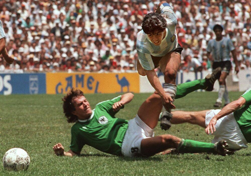 Capitão da equipe, jogador argentino Diego Maradona, dribla jogador da Alemanha Ocidental, Lothar Matthaus, durante a final da Copa do Mundo. A Seleção da Argentina ganhou Alemanha Ocidental por 3 a 2 no Estádio Azteca, Cidade do México, México. A lenda do futebol Diego Maradona faleceu em 25 de novembro de 2020