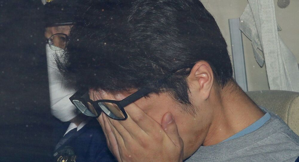 Takahiro Shiraishi cobre o rosto dentro de um carro de polícia em Tóquio em novembro de 2017