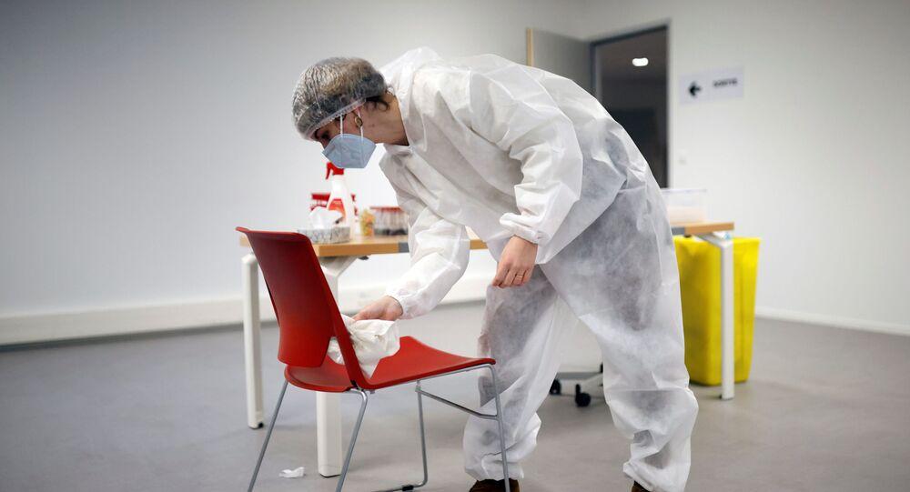Um médico de macacão de proteção e máscara desinfecta uma cadeira no centro de testes de coronavírus em Rezé, França, 15 de dezembro de 2020