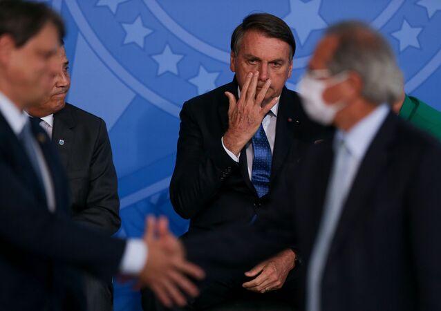 Ministros Tarcísio Freitas (Infraestrutura) e Paulo Guedes (Economia) se cumprimentam durante evento na presença do presidente brasileiro, Jair Bolsonaro (arquivo)