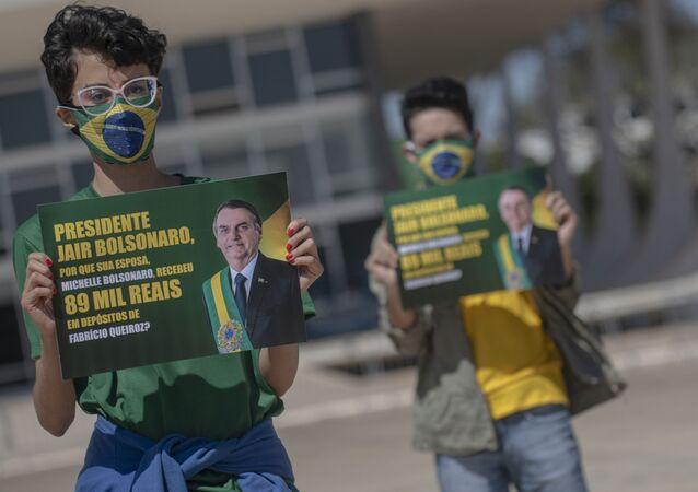 Manifestantes protestam contra o governo do presidente Jair Bolsonaro e exibe cartaz com a frase Presidente Jair Bolsonaro, por que sua esposa, Michelle Bolsonaro, recebeu 89 mil reais em depósito de Fabrício Queiroz?, em frente ao Palácio do Planalto, Brasília, 27 de agosto de 2020