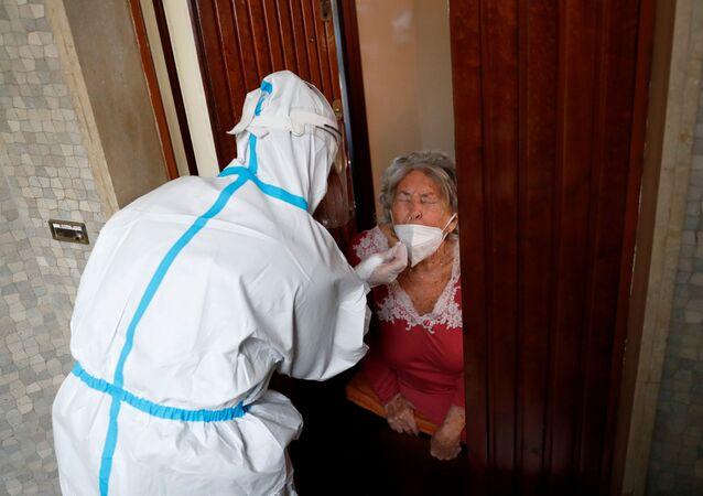 Profissional da saúde fazendo atendimento domiciliar a uma idosa suspeita de ter contraído a COVID-19 em Roma, Itália, no dia 3 de dezembro de 2020