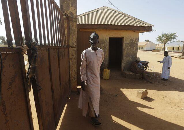 Um segurança na porta da Escola Secundária Estadual de Ciências, onde estudantes foram sequestrados na Nigéria, por rebeldes do grupo extremista Boko Haram