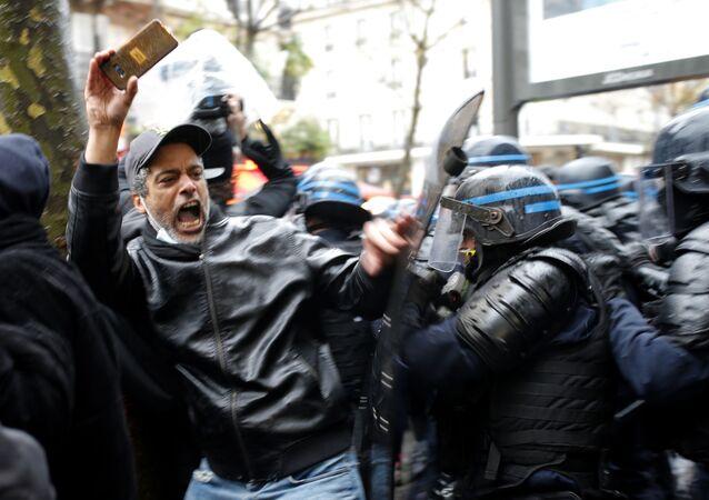 Agentes da polícia de choque atacam um homem que segura seu celular durante um protesto, 12 de dezembro, em Paris, França. Os protestos ocorrem contra uma proposta de lei que tornaria mais difícil para uma testemunha filmar policiais