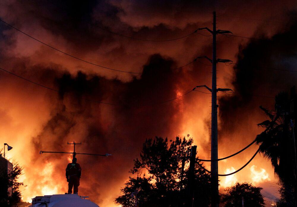 Um bombeiro está sobre um tanque de água durante o fogo na instalação de reciclagem de sucata metálica da empresa Deacero em Guadalupe, México, 16 de dezembro de 2020