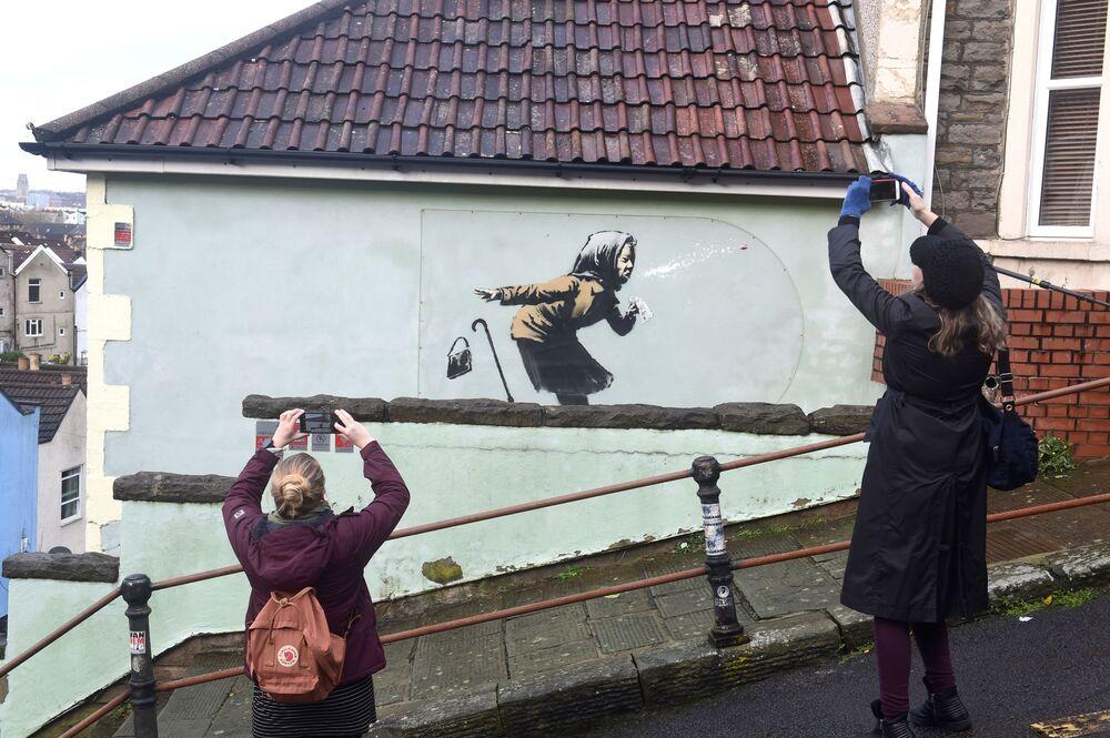 Pessoas tiram fotos da nova obra de arte de rua de Banksy, intitulada Aachoo!!, em Totterdown, Bristol, Reino Unido, 11 de dezembro de 2020