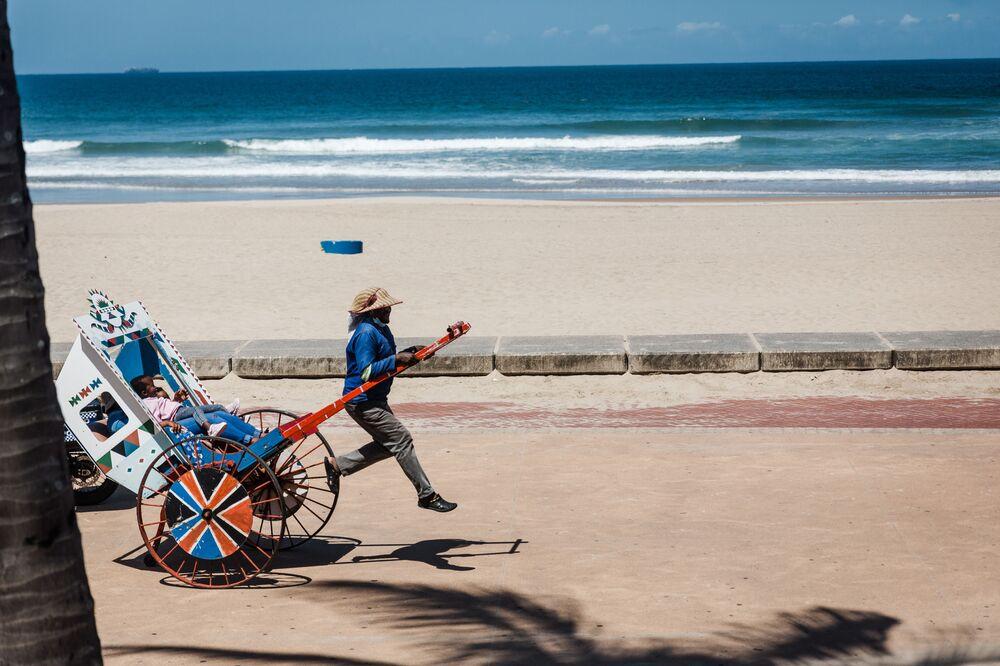 Puxador de riquixá se ocupa de seu negócio com turistas na praia North Beach, Durban, África do Sul, depois de restrições impostas pelo governo proibirem as pessoas de nadarem na costa devido à segunda onda da COVID-19, 16 de dezembro de 2020