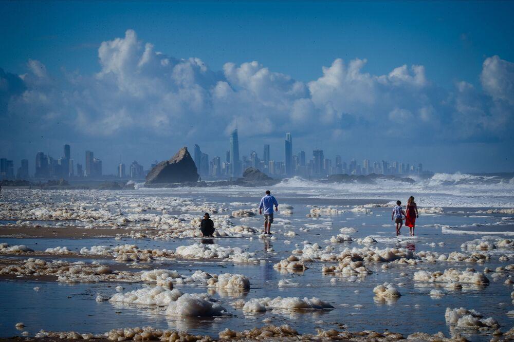 Turistas caminham na espuma marinha depois das condições ciclônicas na praia Currumbin Beach, Austrália, que provocaram chuva e vento fortes nas regiões de Nova Gales do Sul e Sudeste de Queensland, 15 de dezembro de 2020