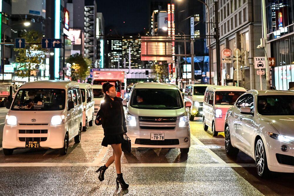 Mulher usando máscara atravessa a rua em Tóquio, Japão, 16 de dezembro de 2020