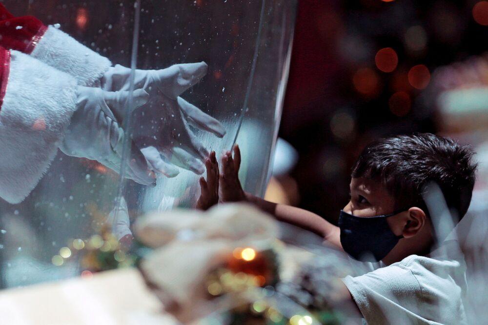 Abilio da Cruz Pinto, 77, vestido de Papai Noel dentro de bolha de plástico, cumprimenta uma criança em centro comercial durante surto da COVID-19 em Brasília, Brasil, 15 de dezembro de 2020