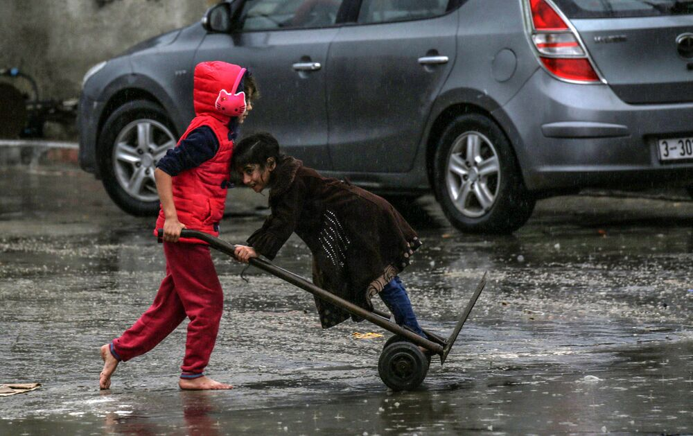 Menina palestina empurra outra montando um carro de mão durante um dia chuvoso no sul da Faixa de Gaza, 16 de dezembro de 2020
