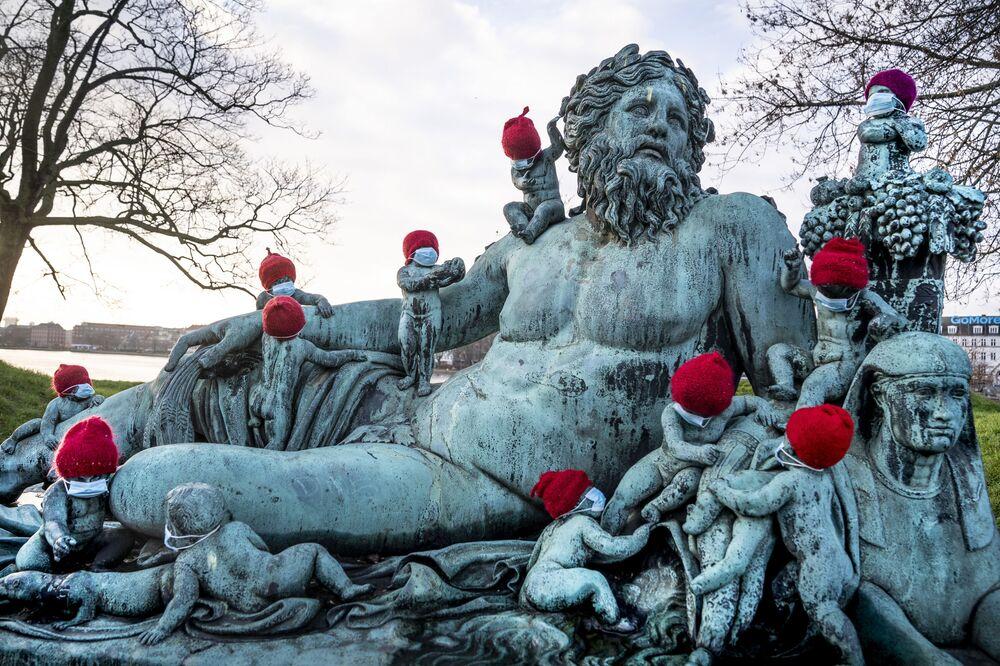 Estatuetas de bronze na estátua de Nilen em Copenhague, Dinamarca, usando gorros vermelhos e pequenas máscaras, 16 de dezembro de 2020